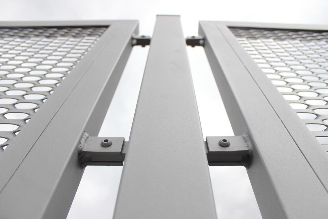 Ocelový sloupek mezi plotovými dílci z tahokovu